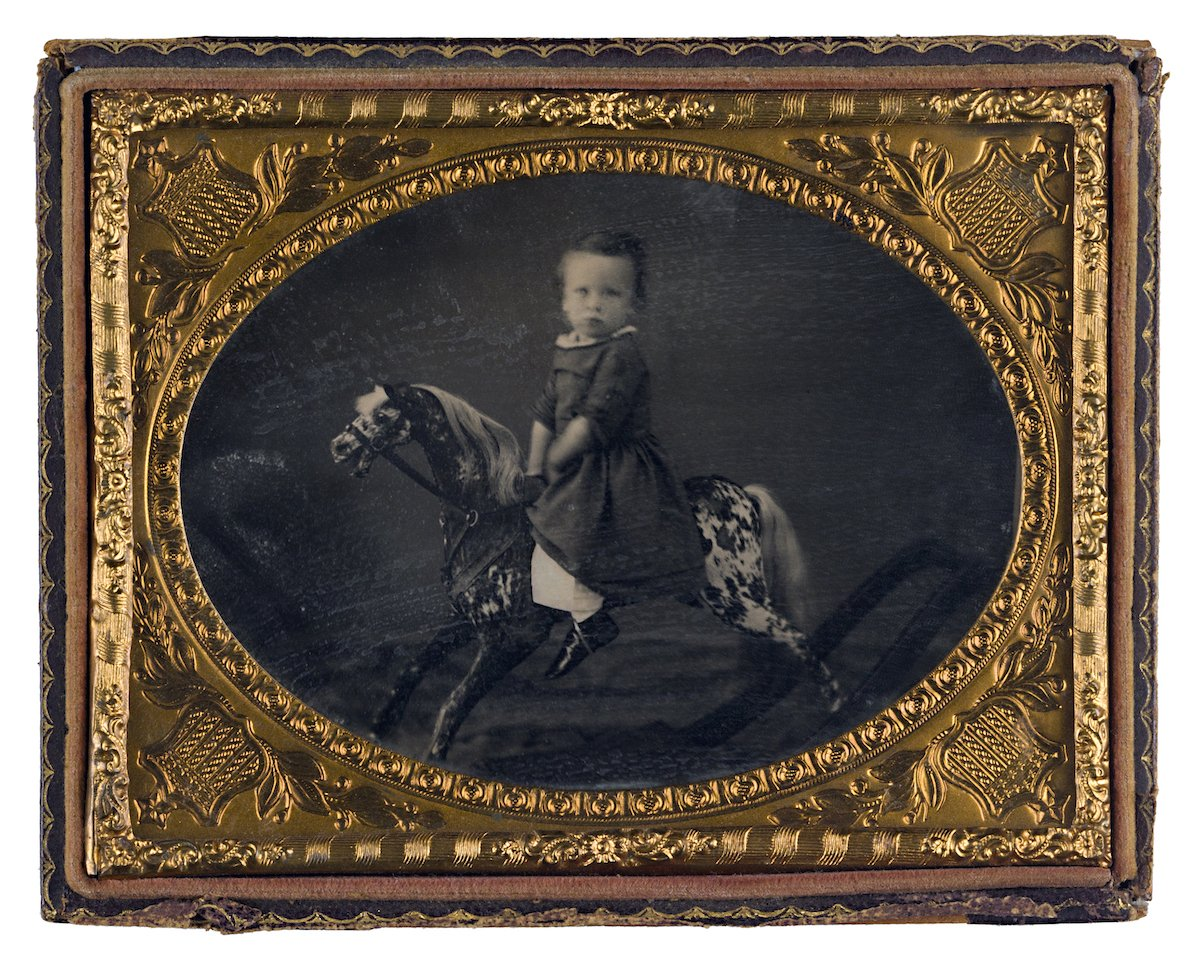 Portrait of a child on a rocking horse circa 1855 by an unidentified photographer.